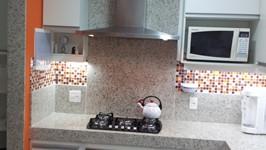 iluminação na área de cocção e painel de granito atrás do fogão