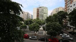 Vista da Janela com praça em rua movimentada