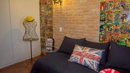 parede de tijolos e painel adesivado com capas de gibis