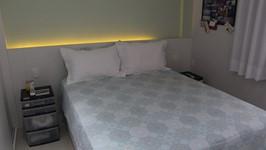 suíte do casal com painel iluminado atrás da cama