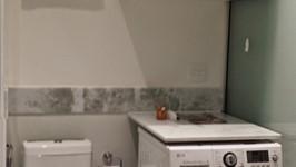 máquina de lavar ao lado do sanitário