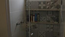 box com cerâmica estampada e nicho no banheiro do casal