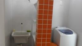 pilar existente revestido de cerâmica laranja dividindo a área de serviço