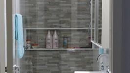 banheiro da suíte do casal com cerâmica imitando canjiquinha e nicho no boxe