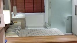 cama com bancada da pia ao fundo e banheiro de vidro