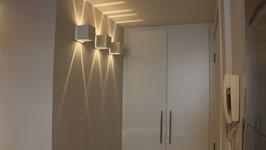 [Hall de Entrada] -  No pequeno hall de entrada, o espaço atrás da porta, ganhou um armário para vassouras, tábua, escada, etc.  A iluminação com arandelas que desenham luz na parede e teto dão as boas vindas a quem chega.