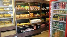 Estante de produtos no corredor entre a padaria e o restaurante