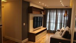 [Sala de Estar] - A sala recebeu um confortável sofá, painel e rack para TV, uma mesa lateral e uma linda luminária pendente sobre a mesa lateral. A cortina escura porém com transparência dá ao ambiente o conforto e a privacidade necessária.