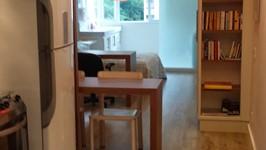 entrada do apartamento com cozinha em fita à esquerda
