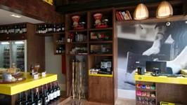 Salão com caixa e pé-direito duplo com passarela de acesso à estande de vinhos.
