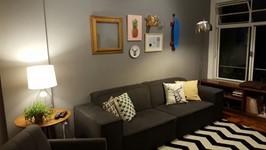 paginação de quadros e peças formando uma montagem na parede do sofá