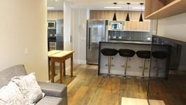 [Cozinha Integrada] - A cozinha integrada à sala, recebeu o mesmo acabamento do mobiliário e o mesmo piso ceramico imitando madeira, para dar continuidade.