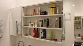 armário do banheiro do casal com portas de espelho de correr abertas
