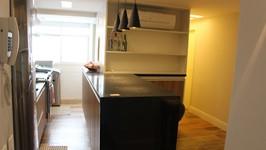 [Cozinha Integrada] - O  balcão de refeições para 3 pessoas ganhou uma estante com armário para bebidas e copos na parte de sala e um armário para louças na parte da cozinha.