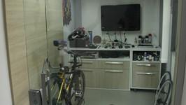 bancada de trabalho, TV na parede e gaveteiro com rodízios