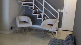 Poltronas giratórias a puffs criam mais lugares para as visitas ficarem a vontade na sala.