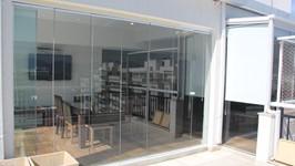 Ampliação do lounge na área da churrasqueira com cobertura de vidro.
