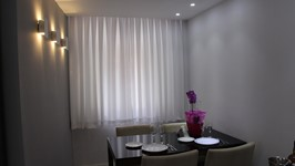 Sala de jantar com arandelas que funcionam como adorno na parede