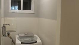 área de serviço com tanque, secador de roupas de teto e máquina de lavar