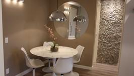 mesa redonda e cadeiras saarinen, espelho redondo, arandelas e luminária pendente decorando o espaço de refeições