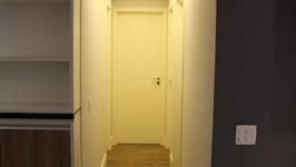 [Iluminação] - O corredor para os quartos fica no meio da sala e lâmpadas embutidas nos rasgos desenhados para o teto de gesso ajudam a unir o corredor à sala, numa decoração bem mais alegre.