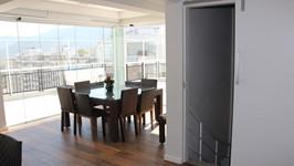 Piso de madeira e fechamento de vidro no novo lounge do terraço