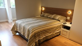 painel da cama em madeira com arandelas e criado mudo.