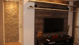 parede revestida de pedra portuguesa branca no pequeno hall entre a sala e a cozinha