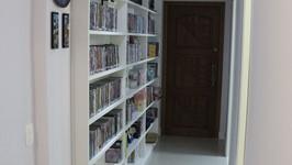 Hall de entrada com estante de CDs, DVDs e coleções