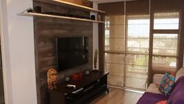 painel da TV com rack baixo e sofá confortável na área do living