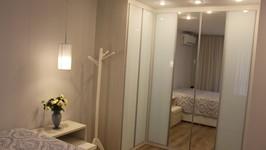 """armário em """"L"""" com portas de espelho substitui o closet e amplia a suíte"""