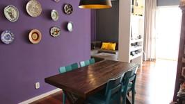 mesa de jantar e painel com coleção de pratos