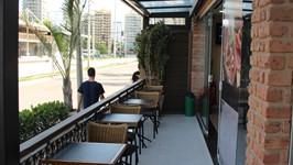 Varanda coberta com mesas e cadeiras