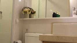espelho contínuo sobre a louça sanitária para ampliar o espaço. A estante flutuante embaixo do espelho apoia produtos e perfumes
