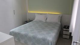 Painel iluminado atrás da cama do casal