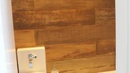 Parede de cerâmica imitando madeira e bancada com cuba descentralizada