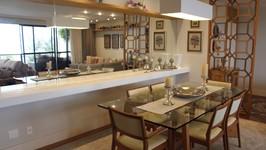 mesa de jantar com grande console de pedra e espelho que reflete o mar