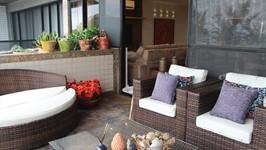 lounge da varanda com plantas no canteiro lateral